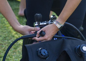 Close view of the hands of a diver preparing his diving equipment